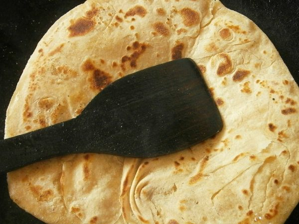 Next, press lightly all over to blow up the chapati.